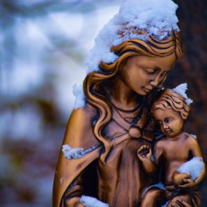 brown mother and child statue partially covered with snow